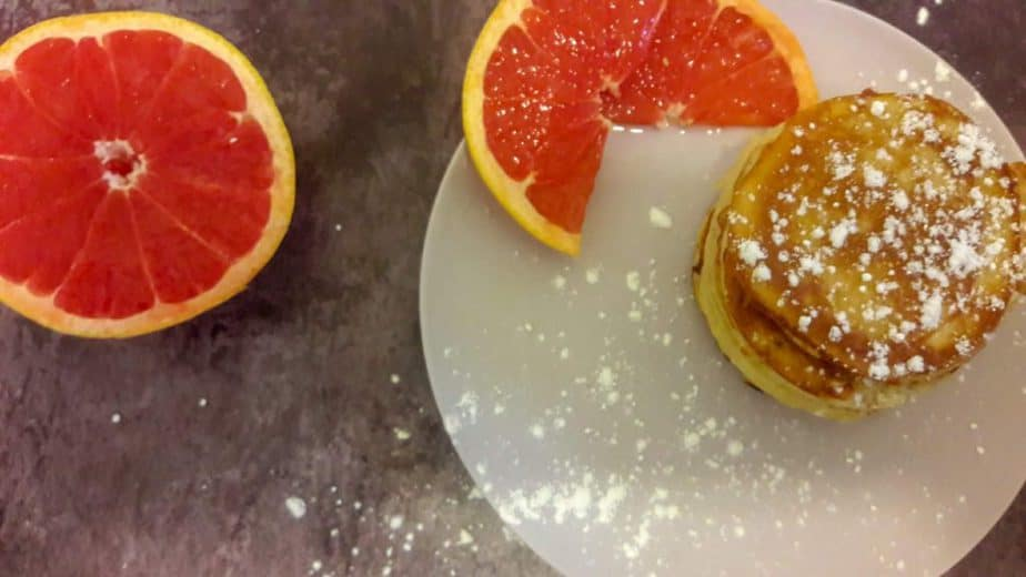 A stack of confectioners sugar-dusted pancakes on a plate with some sliced grapefruit.