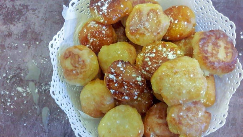 A white bowl full of glazed donut holes.