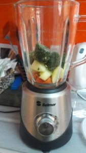 Carrots, apples, and spinach in a blender.
