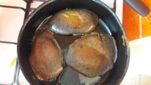 Frying pan with three chocolate hidden vegetable pancakes after they have been flipped.