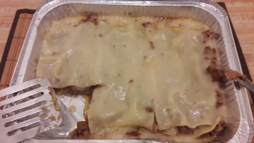 Cooked meat lasagna in aluminum pan with a piece cut out of it ~ bitesnpieces.co