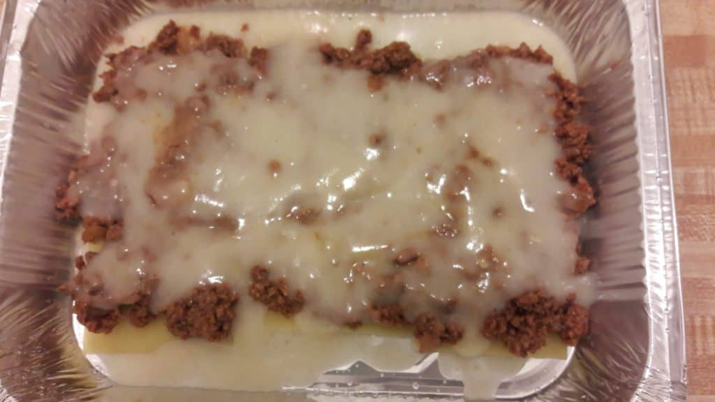 Lasagna noodles, chopped meat, bechamel sauce layered in aluminum baking pan ~ bitesnpieces.co