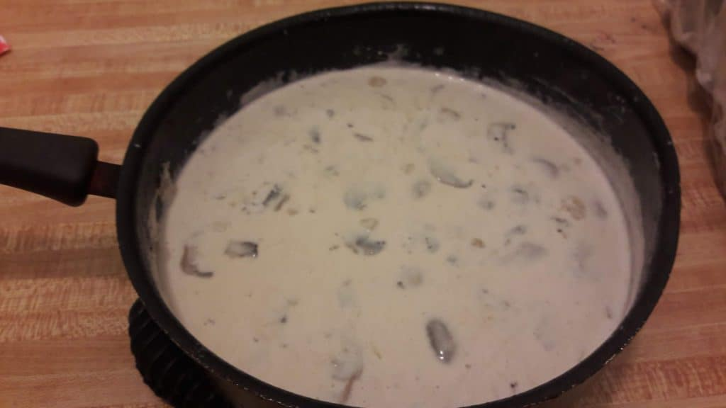 Completed Alfredo sauce with mushrooms in a saucepan on the table