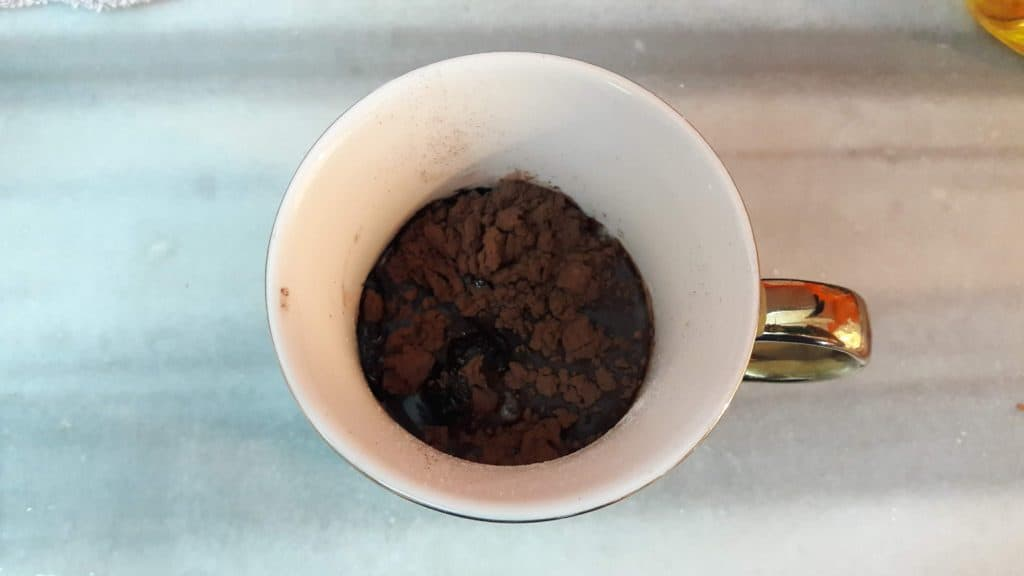 Overhead shot of a mug containing the unmixed ingredients for brownie in a mug