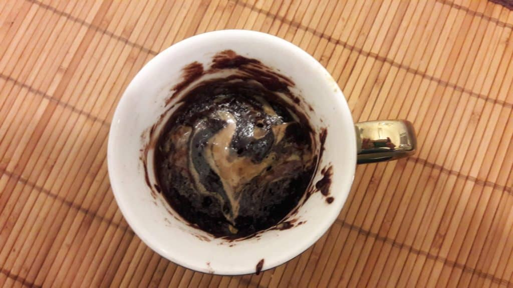 Overhead shot of brownie in a mug with a swirl of peanut butter in the brownie