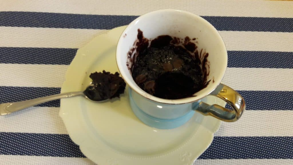 Mug containing brownie sitting on a plate. Resting on the plate next to it is a spoon with a spoonful of brownie in it.