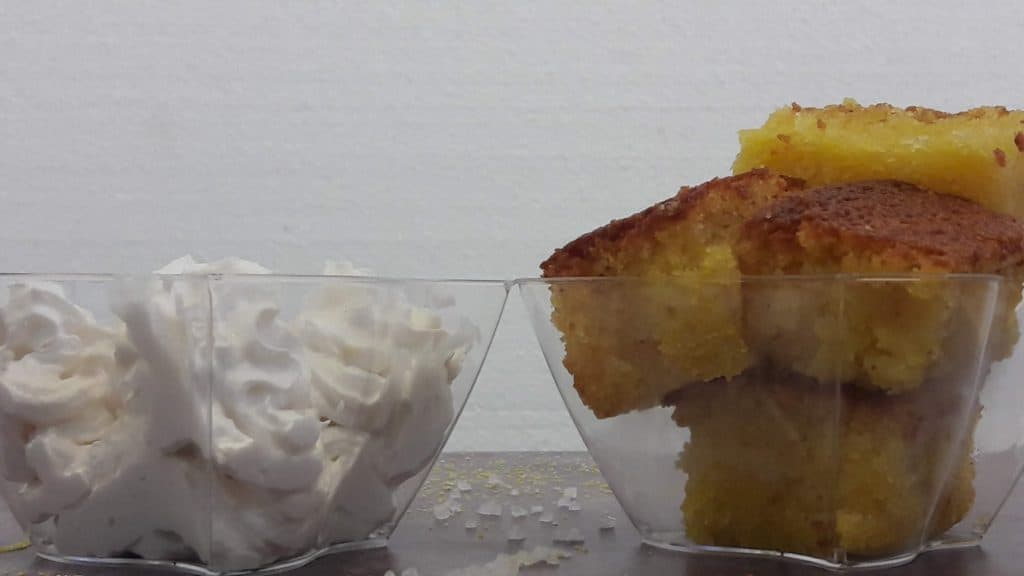 Side view of a bowl of cut up cornbread and a bowl of whipped cream