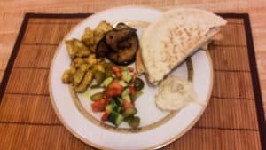 A plate holding the chicken shawarma, fried eggplant, sliced vegetables, hummus, and pita.