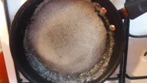 Sugar-water syrup in the frying pan on the stove.