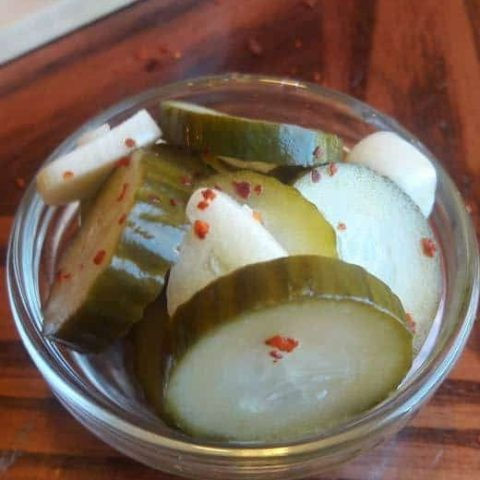 small glass bowl of pickles, with a head of garlic in the background.
