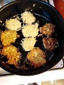 Latkes frying in a frying pan.