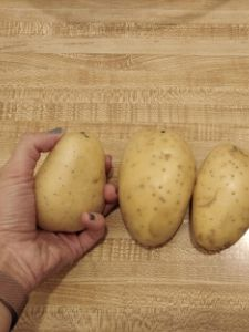 A hand holding a potato, with two more potatoes on the table next to it.