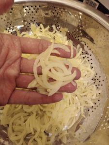 A hand holding some spiralized potato shreds.
